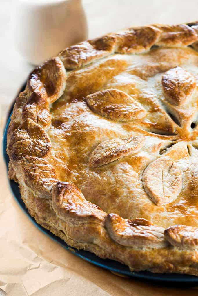 An apple pie fresh from the oevn with a jug of caramel saucee brackground