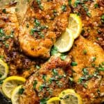 golden chicken breasts in a pan with sauce and lemon slices