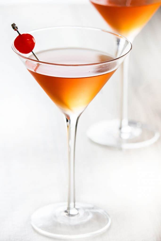 two cocktail glasses with manhattan drink and a cherry