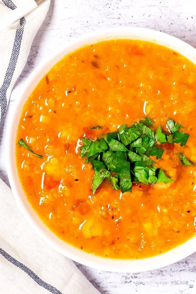 an overhead shot of red lentil soup in a bowl with garnish.