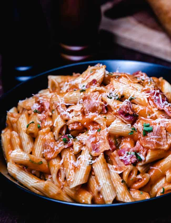 a bowl of tomato cream sauce on pasta.