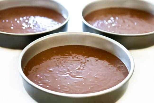 three cake pans with chocolate cake batter