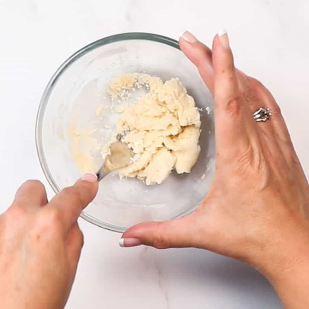 flour and butter being mixed in a glass bowl