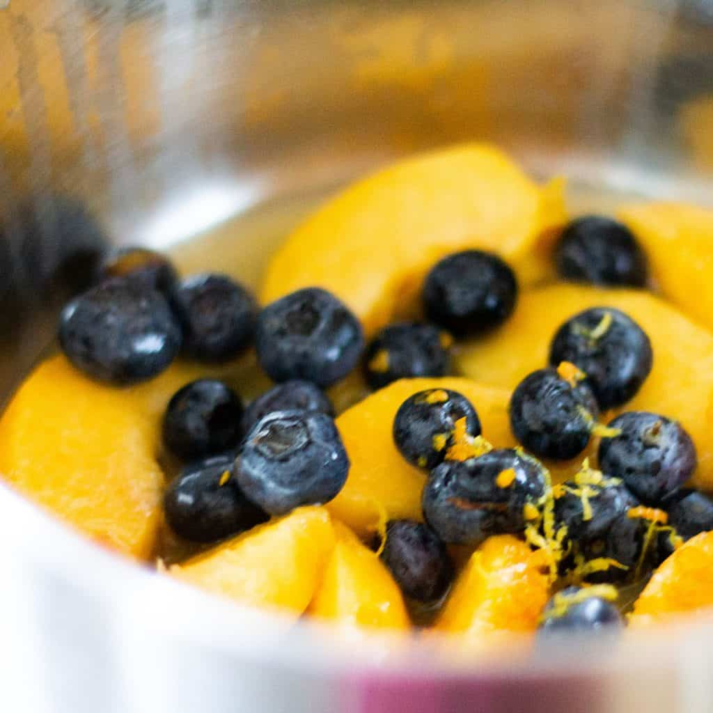 peaches and blueberries in a metal bowl with grated orange zest