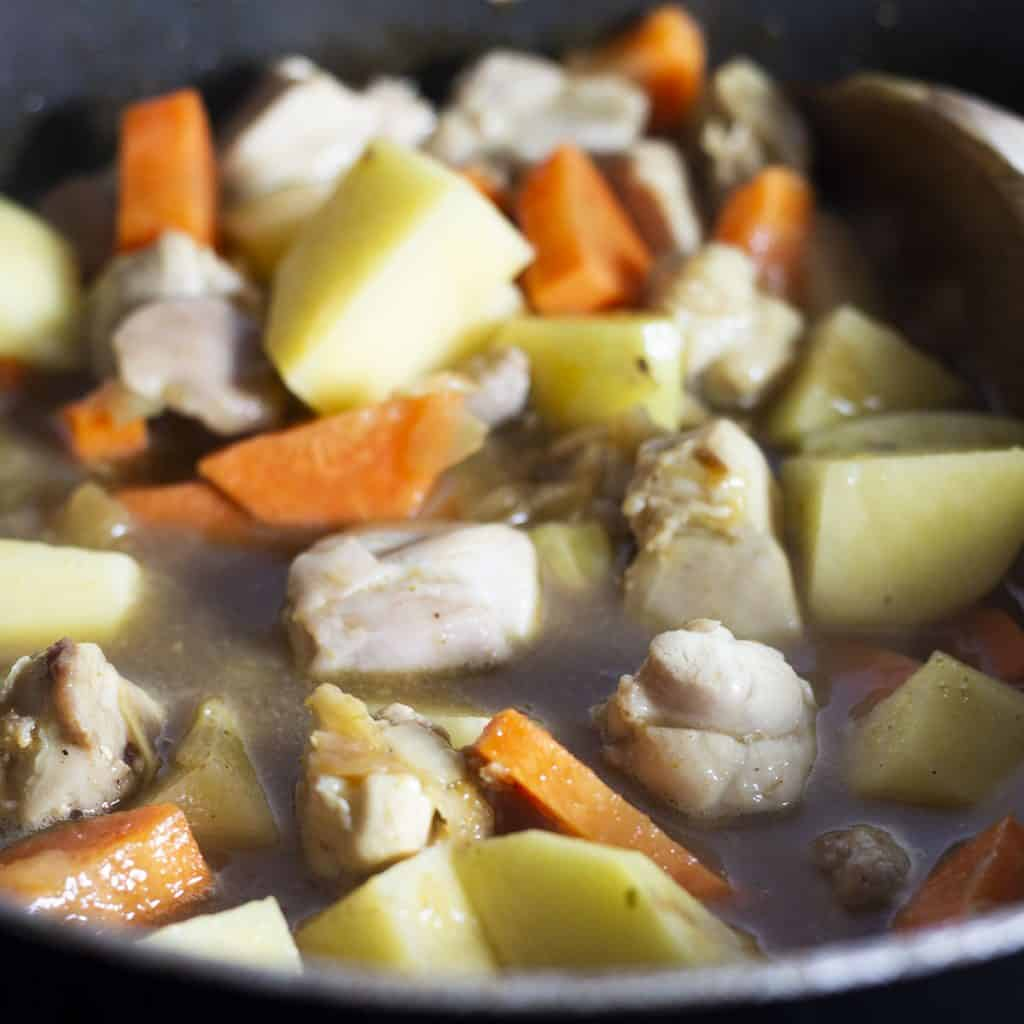 The potatoes and carrots added to the pot with the chicken