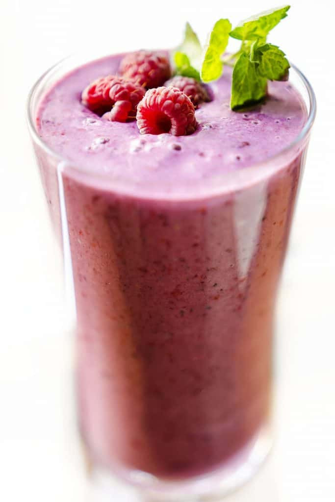 a glass of raspberry smoothie with raspberries and mit
