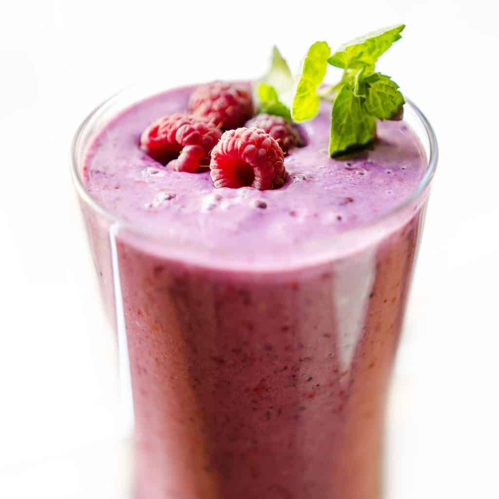 raspberry smoothie topped with raspberries and a sprig of mint for decoration