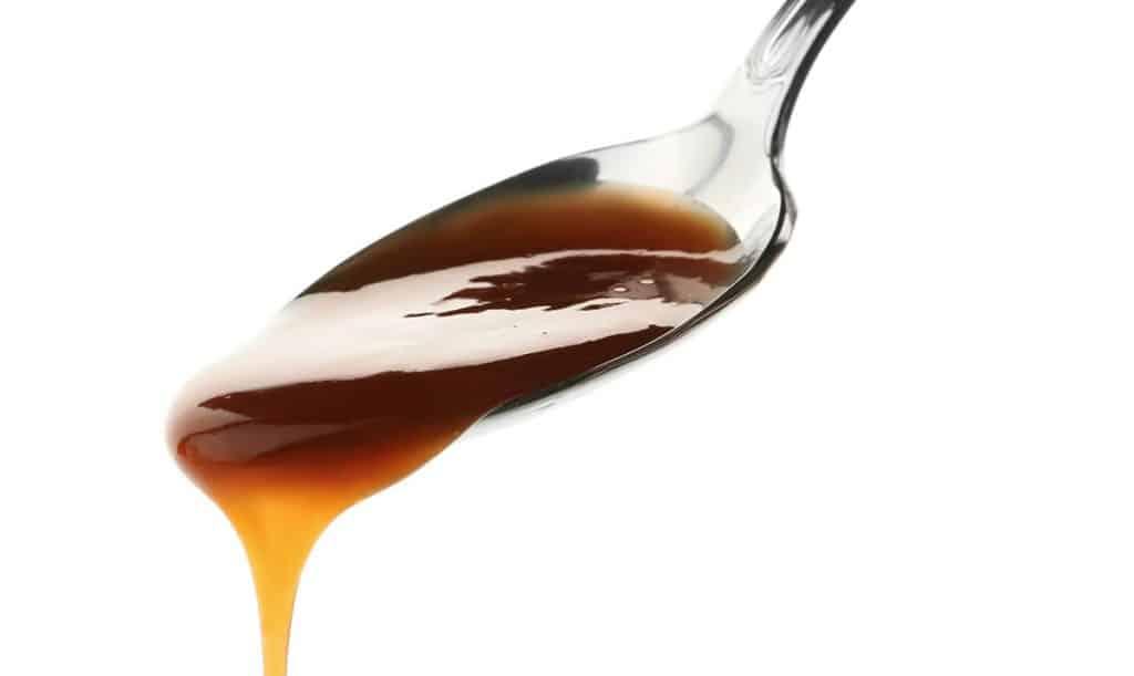 A spoon of caramel sauce