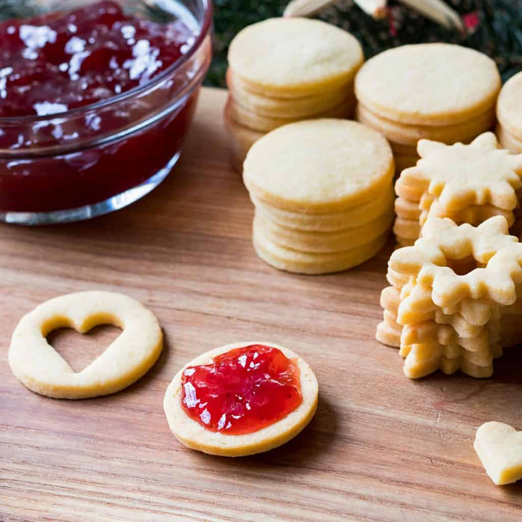 Preparation of traditional Linzer Christmas cookies - filling the cookies with jam