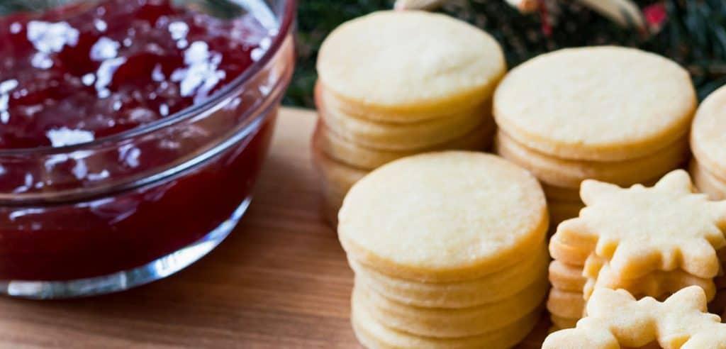a jar of jam next to cookies