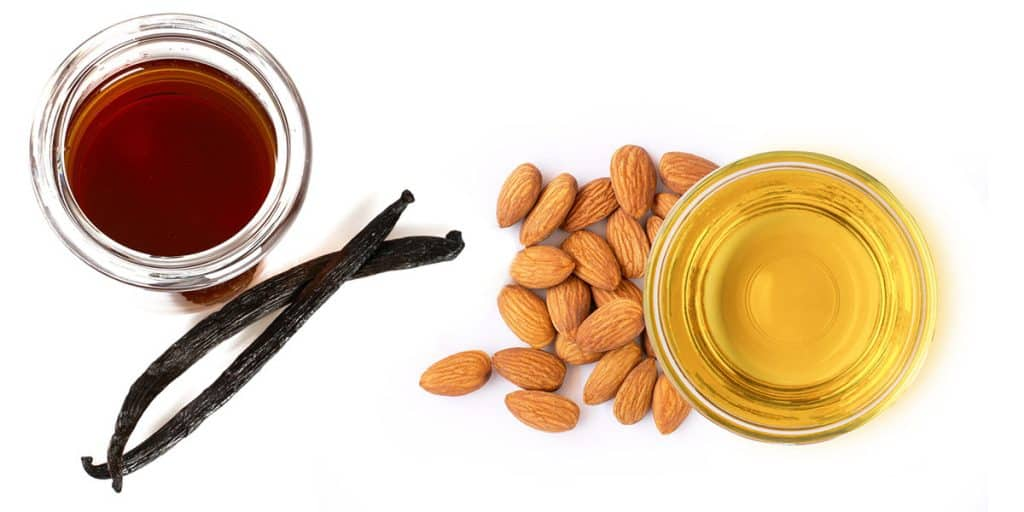 a bowl of vanilla extract with vanilla pods and a bowl of almond extract with almonds