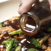 stir fry sauce being poured onto chicken and broccoli