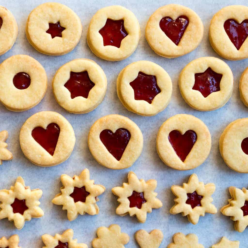 Traditional Linzer cookies filled with jam on parchment paper