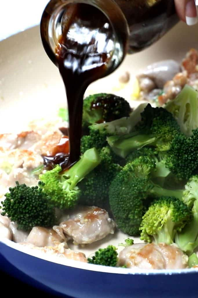 stir-fry sauce being poured into the pan with the chicken and broccoli mixture