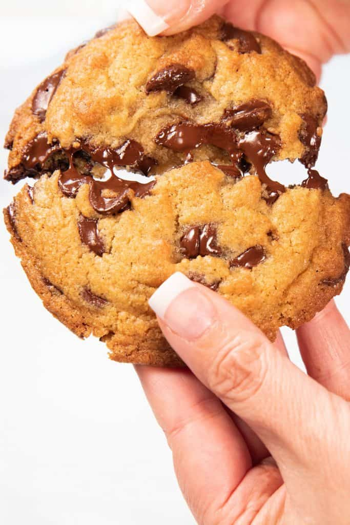 a freshly baked cookie being broken open to show melted chips