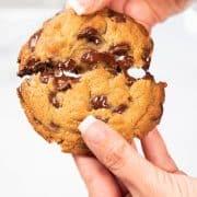 a chocolate chip cookie being broken in half