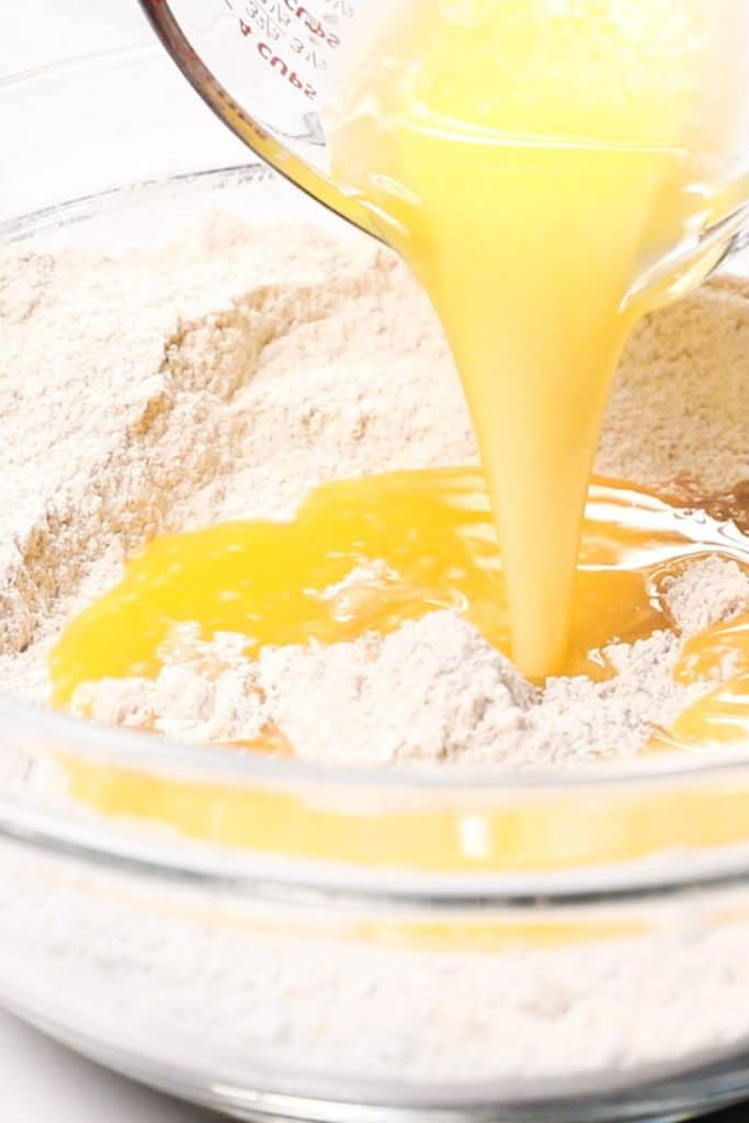 melted butter being added to the dry ingredients for cookies