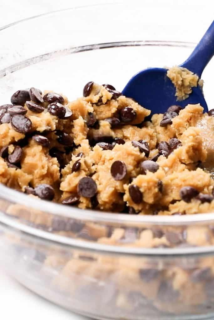 chocolate chips being mixed into cookie dough