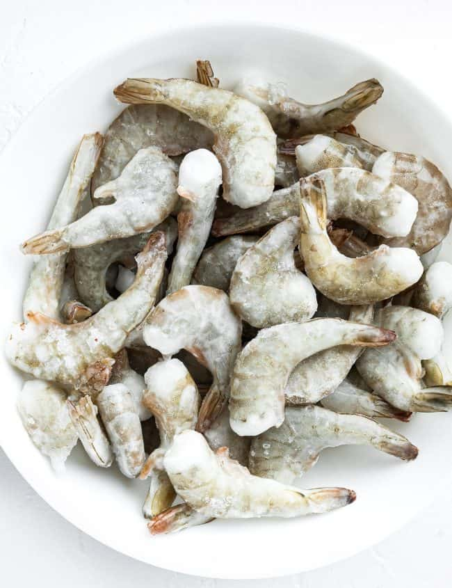 Frozen raw uncooked tiger shrimp on white stone surface, top view flat lay, square format