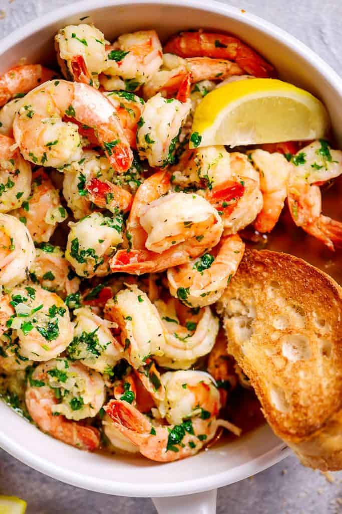 top view garlic butter shrimp in a white frying pan with bread and lemon