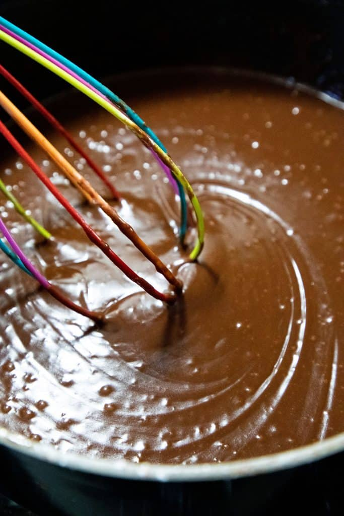 chocolate frosting being mixed in a pan