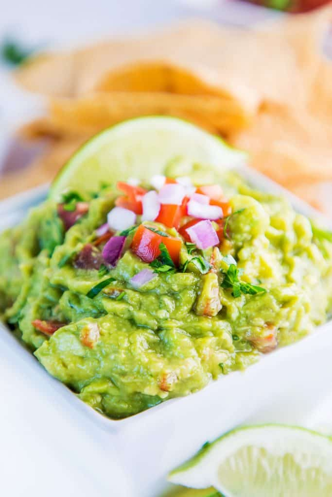 a bowl of guacamole with sliced lime on top