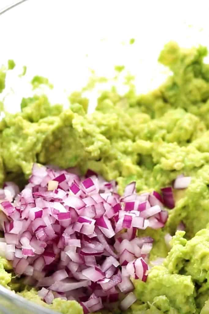 diced red onion added to mashed avocado