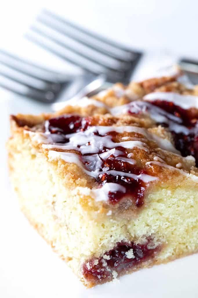 a slice of cake with rapberry jam and icing