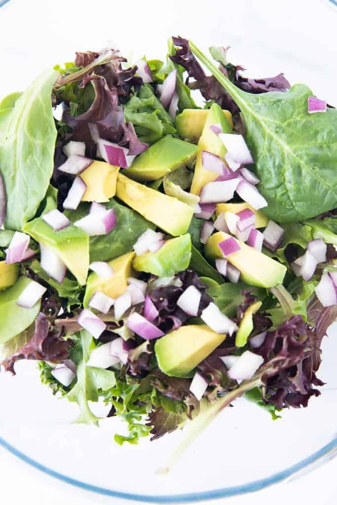 salad greens, red onion and diced avocado in a bowl