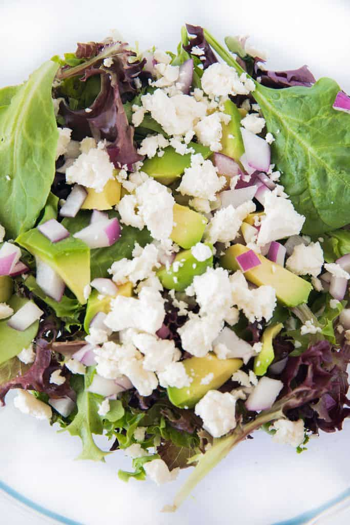 a bowl with salad greens, avocado, red onion and feta cheese