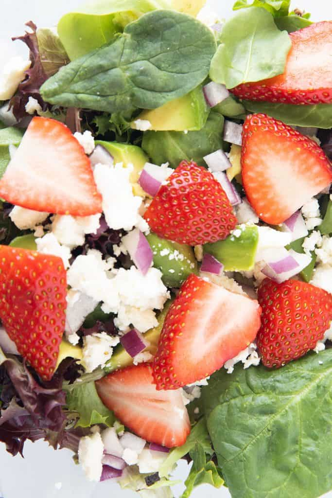 strawberries added to green salad, red onion, feta cheese and avocado