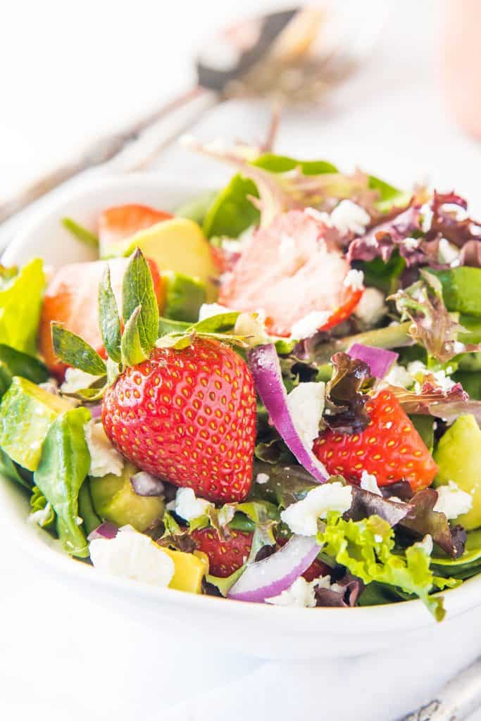 a bowl of salad with strawberries