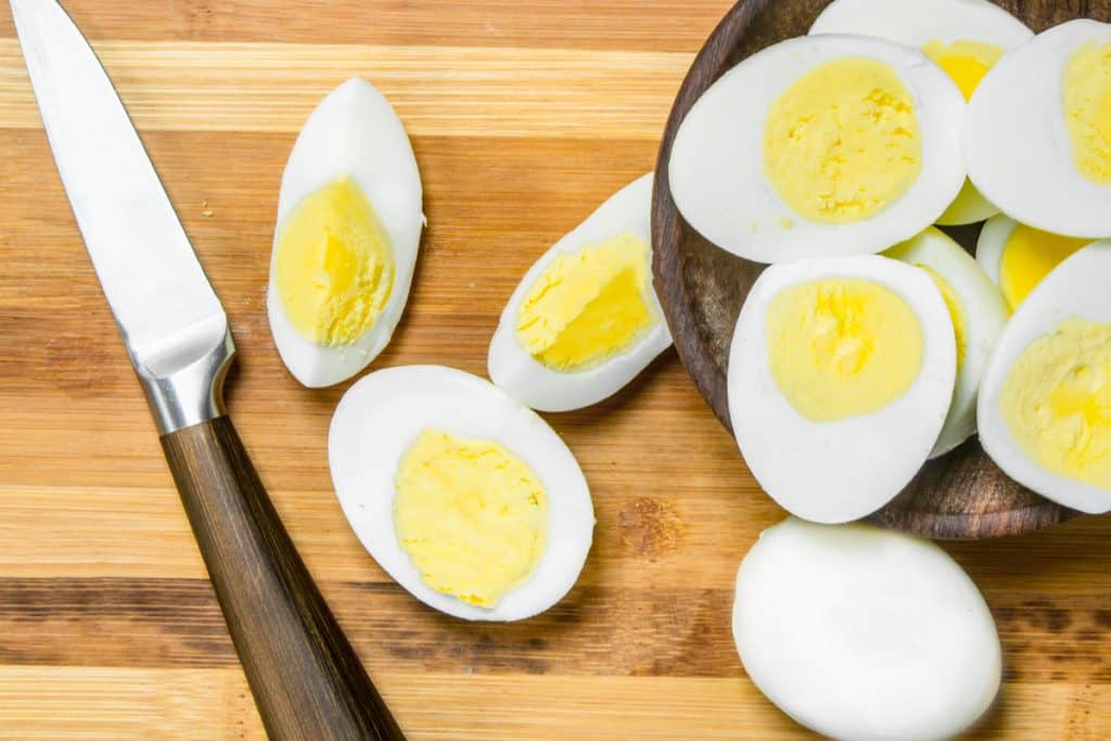 Sliced boiled eggs on cutting board. On a wooden background.