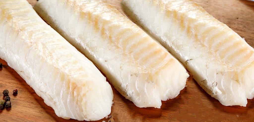 Fresh raw cod fillet on cutting board