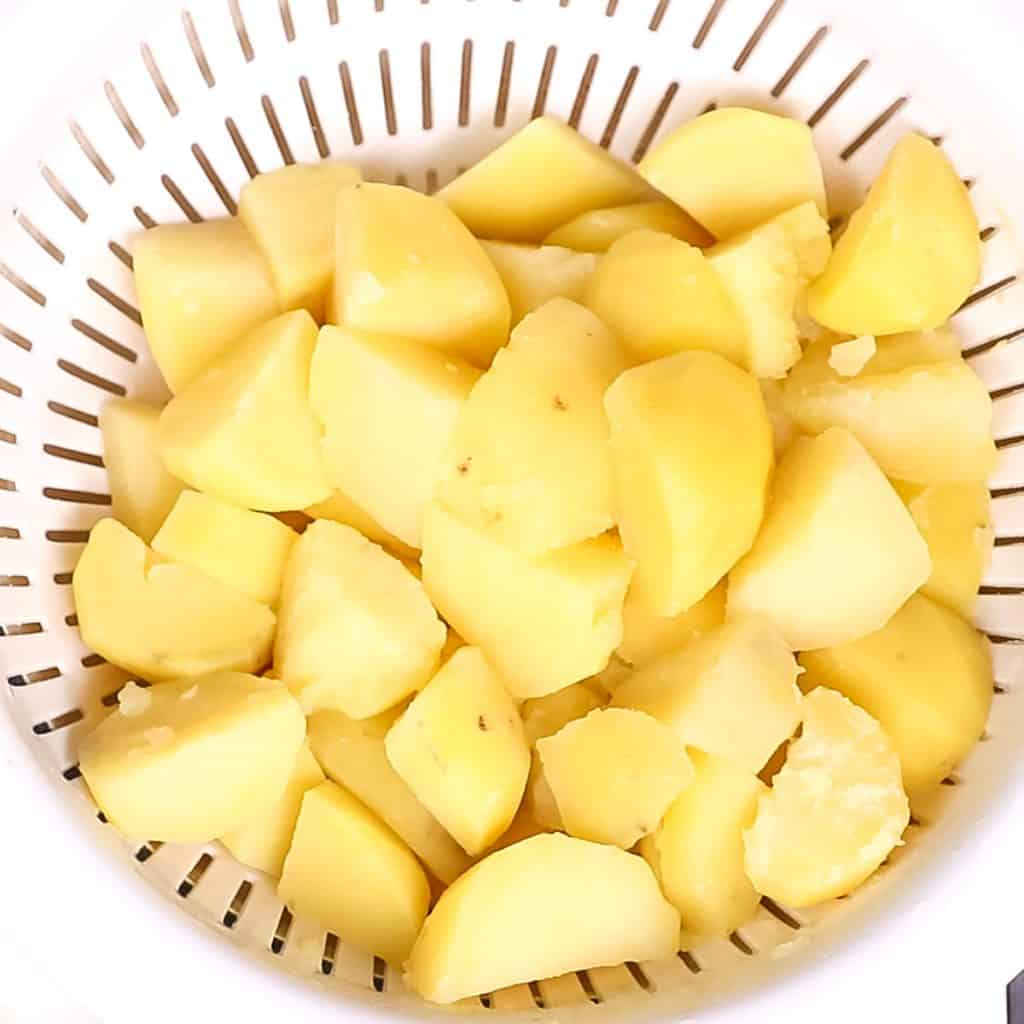 cooked potatoes in a strainer