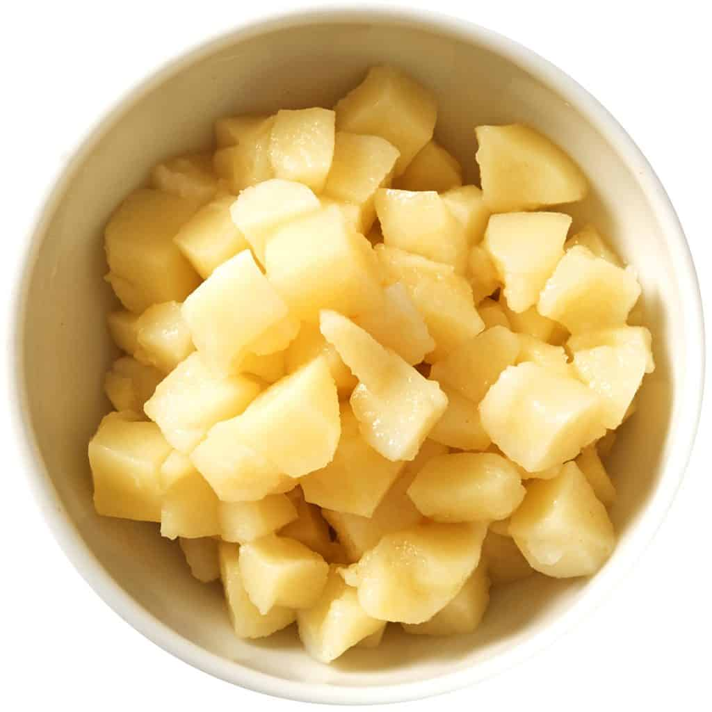 cooked potatoes in a bowl dressed with vinegar