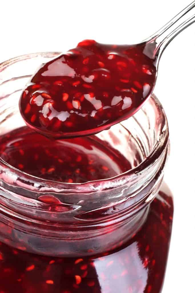 Raspberry jam in glass with metal spoon isolated on white