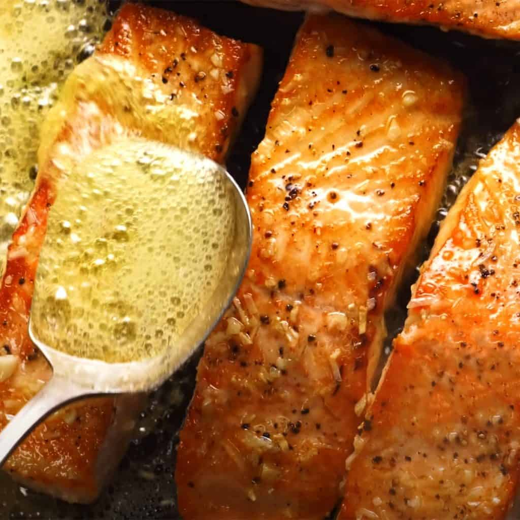 salmon filets being basted with butter