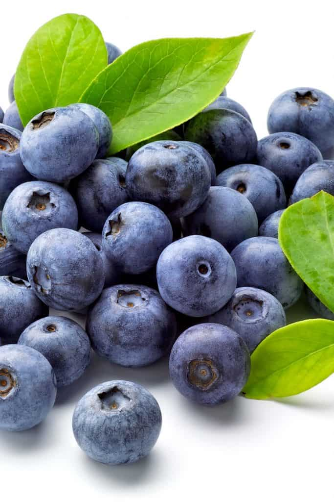 a plie of fresh blueberries with some leaves