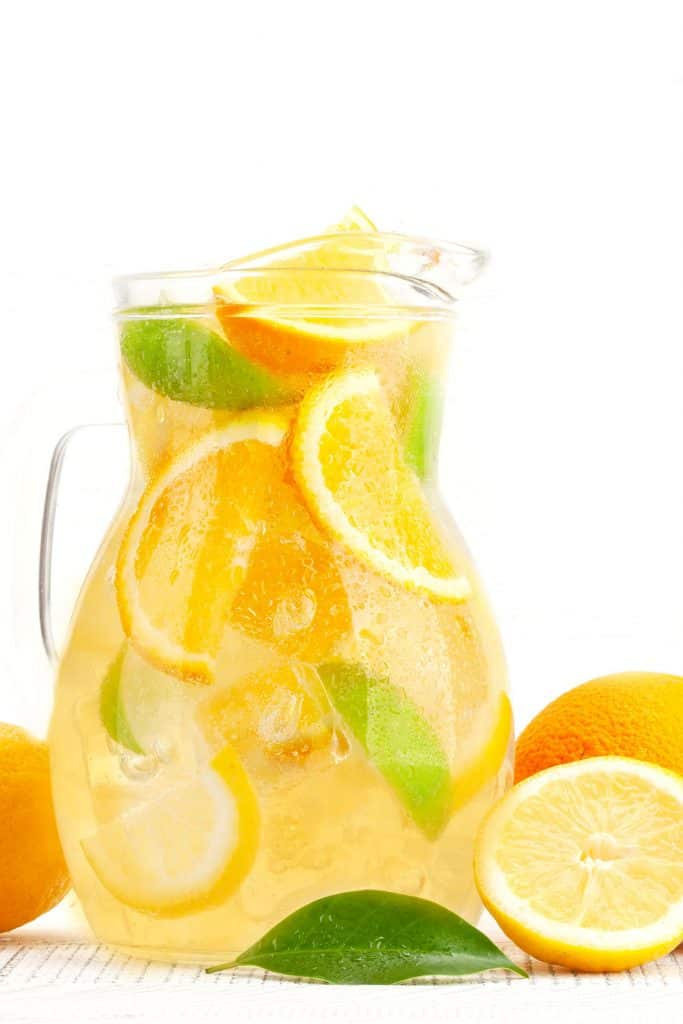 Fresh fruit punch in a glass pitche with citrus fruits around it