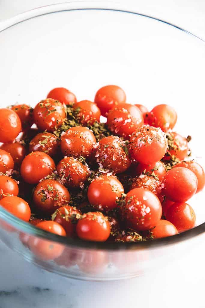 herbs on a bowl of cherry tomatoes