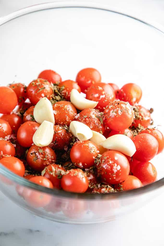 a bowl of cherry tomatoes with garlic cloves