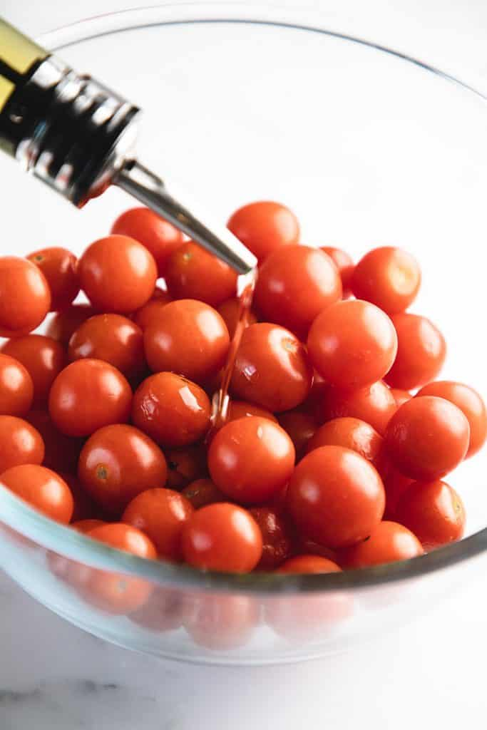 oil being poured onto a bowl of tomatoes