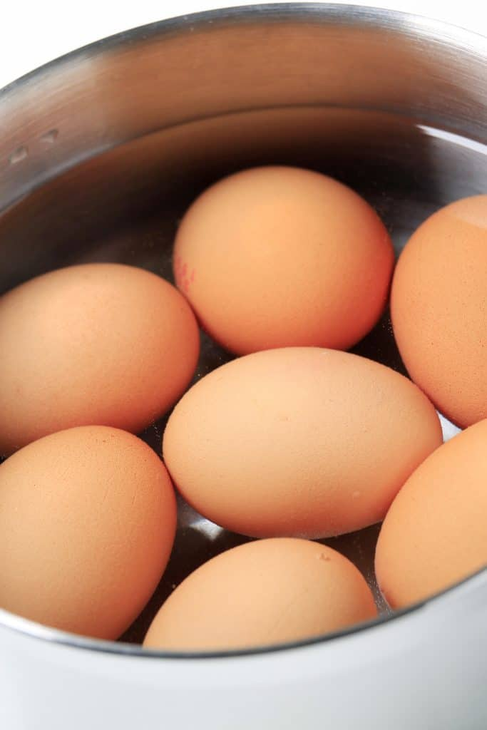 brown eggs in a pot of water