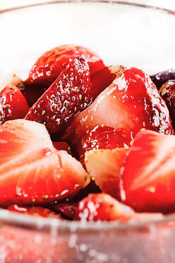 Close up of sliced strawberries in clear glass bowl glazed with