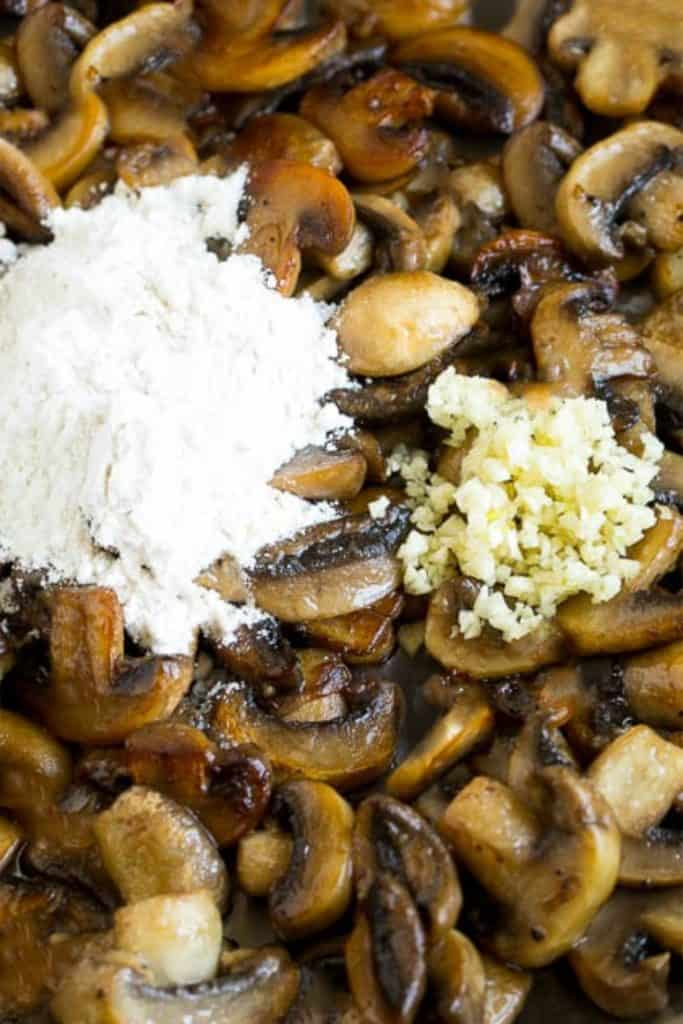 flour and garlic added to the pan with cooked mushrooms