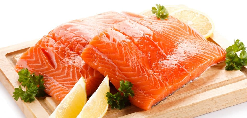 Fresh raw salmon fillet on cutting board on white background