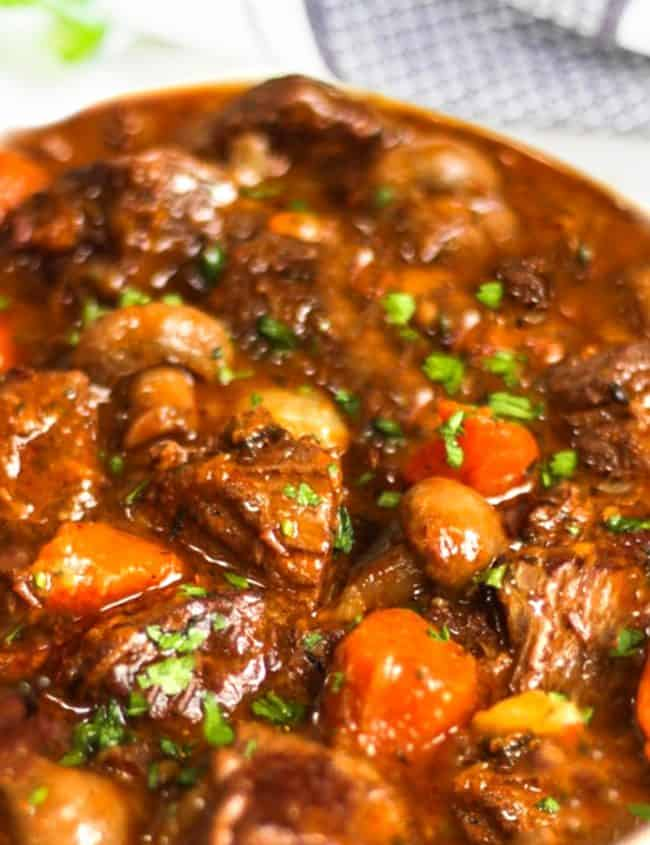 shot of beef stew with herbs in the background