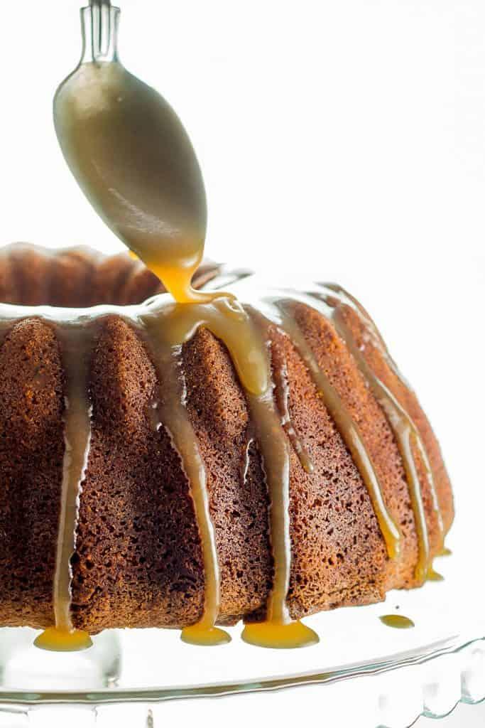 caramel glaze being pored onto a cake with a spoon